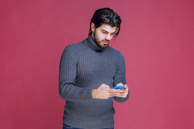 Uomo che tiene uno smartphone, legge messaggi o invia sms.