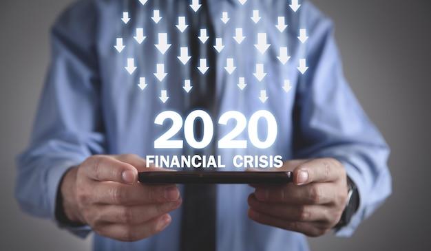 金融危機2020のテキストでスマートフォンを持っている男。