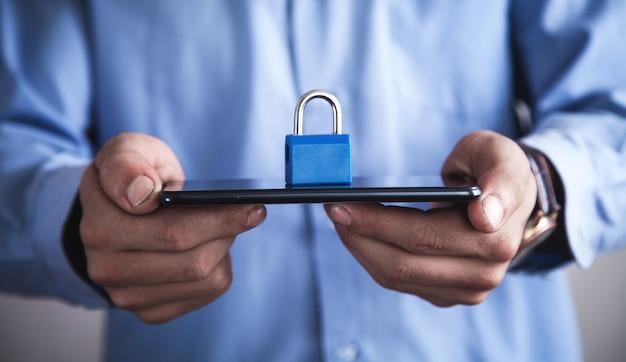 南京錠でスマートフォンを持っている男。モバイルとインターネットのセキュリティの概念
