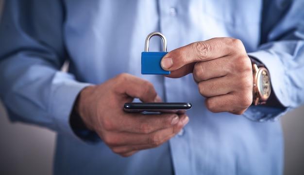 南京錠でスマートフォンを持っている男。セキュリティ