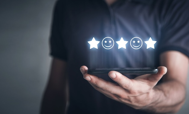 笑顔と星とスマートフォンを持っている男。フィードバック。顧客満足