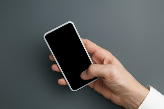 テキストやデザインの灰色の壁に空の画面でスマートフォンを保持している男。