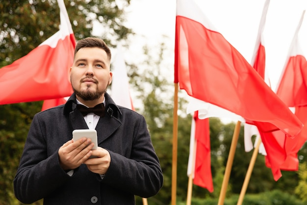 Man holding smartphone with flags of poland behind