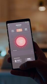 照明制御アプリケーションでスマートフォンを持っている男性、自動照明システムでキッチンハウスに座っているライトをオンにします。ラップトップでリモートで作業するスマートホームソフトウェアを使用している人