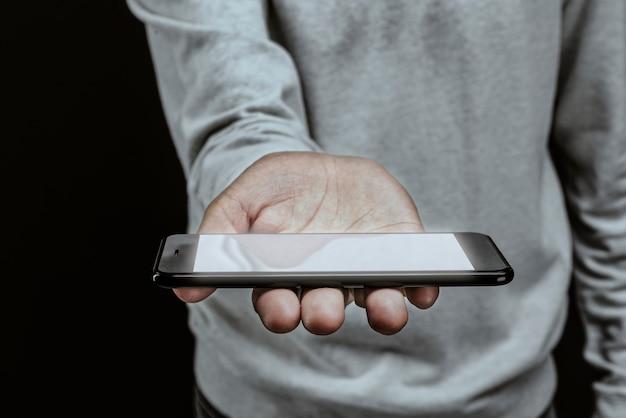 Uomo che tiene smartphone con uno schermo bianco