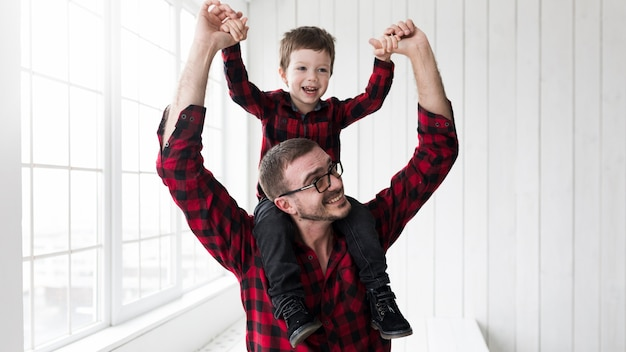 Man holding son on fathers day in front of chalkboard