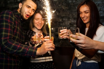 Man holding sparkle candle enjoying drinks with friends