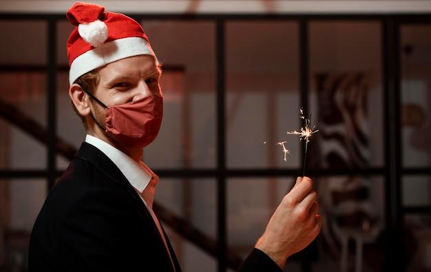 Uomo che tiene un sparkler alla festa di capodanno con lo spazio della copia