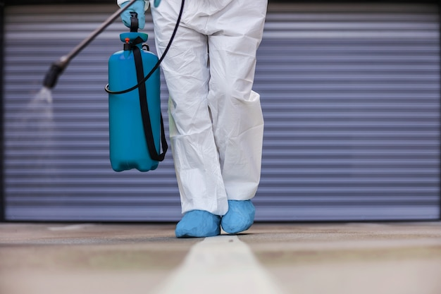 Man holding sprayer with disinfectant and spraying garage in order to prevent spreading coronavirus