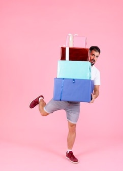 Man holding stack of gift boxes running against pink background