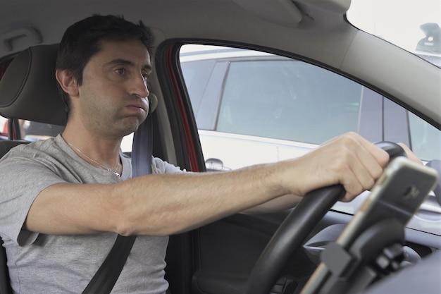 Человек держит руль и мобильный телефон на автомобильном держателе для мобильного телефона