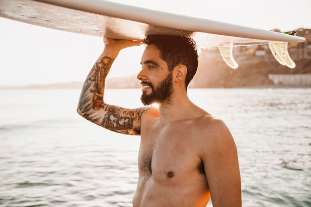 Man holding surfboard on head
