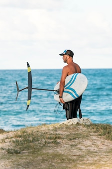 Man holding a surfing board outdoors