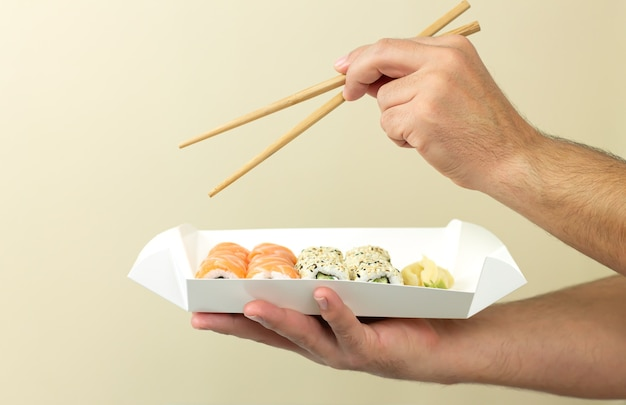 Man holding sushi set in disposable plate and eating japanese food by chopsticks.