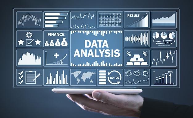 Человек, держащий планшетный компьютер. анализ данных. графики прибыли и анализ тенденций фондового рынка. бизнес. финансы