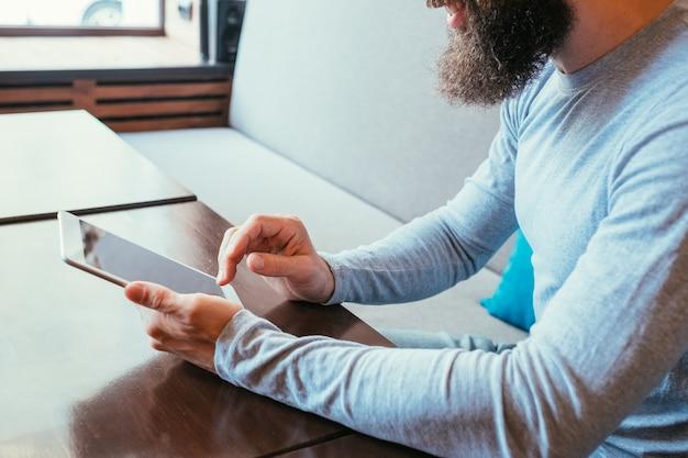 タブレットを持っている男。デジタルデバイスを介したモビリティとオンラインインターネットアクセス。