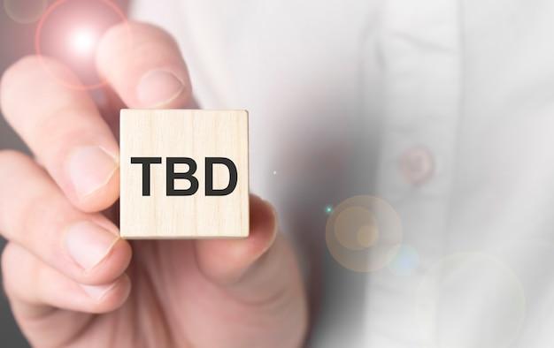 Человек, держащий слово tbd на деревянном кубе.