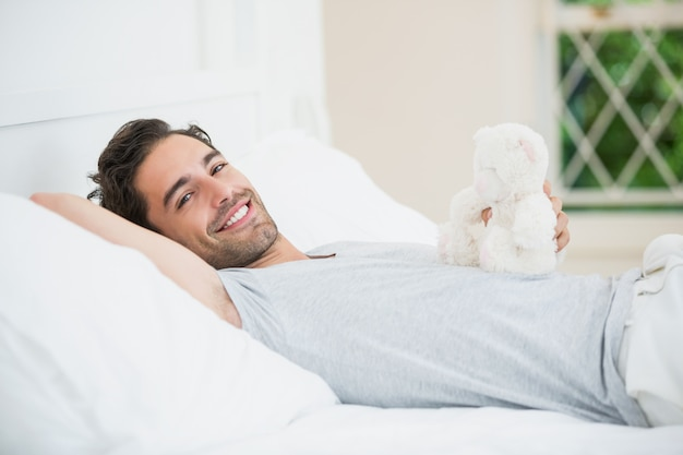 Man holding teddy bear while relaxing on bed