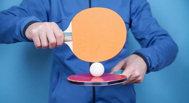 テニスラケットと白いプラスチックボールを持っている男