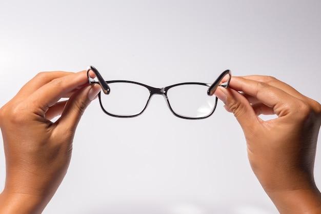 Мужчина держит очки в очках с блестящей черной рамкой на белом