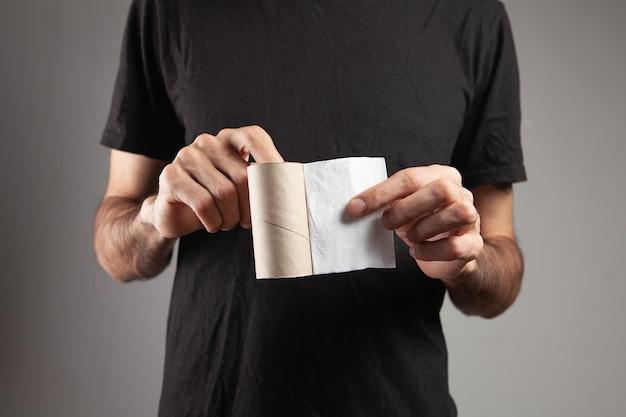 Мужчина держит последний кусок туалетной бумаги на сером фоне