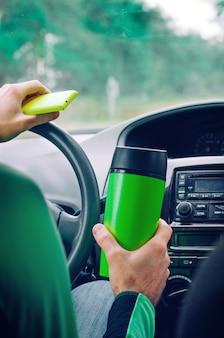 Man holding thermo mug and smartphone