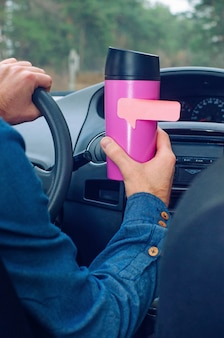 Man holding thermo mug with lipstick