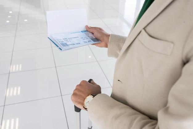 Мужчина держит билеты в аэропорту