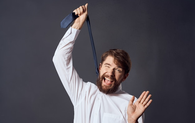 手にネクタイを保持し、自殺灰色の背景モデルのトリミングされたビューを窒息させる男