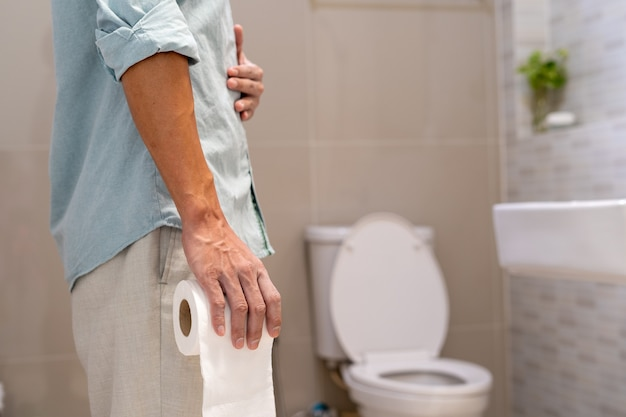 Man holding tissue paper roll standing in front of toilet.
