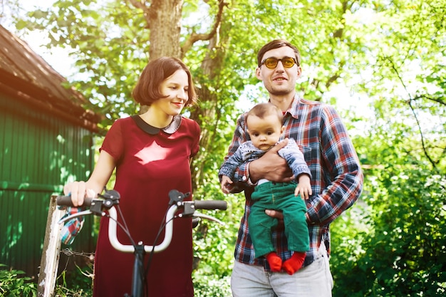 Man holding toddler and woman holding bike