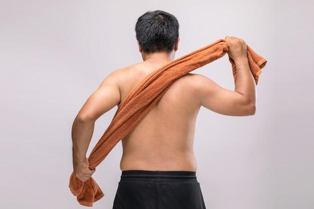 シャワーの後に乾くためにタオルを持っている男