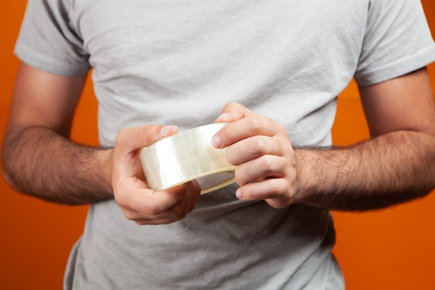 オレンジ色の背景に透明なテープを保持している男