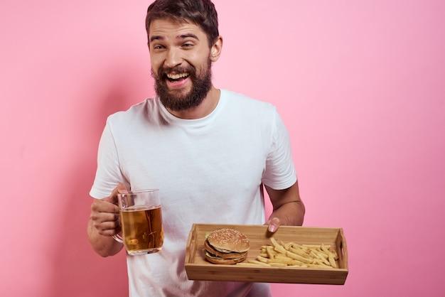 Мужчина держит поднос с картофелем фри и гамбургером