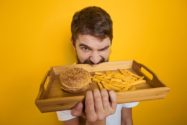 Мужчина держит поднос с гамбургером и картофелем фри