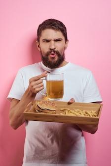 Мужчина держит поднос с кружкой пива, картофелем фри и гамбургером