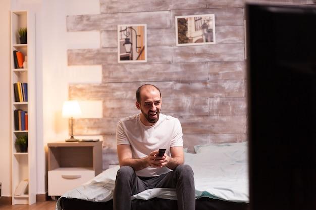 Uomo che tiene il telecomando della tv mentre ride durante uno spettacolo televisivo.