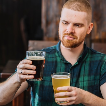 Man holding two different type of alcoholic drinks