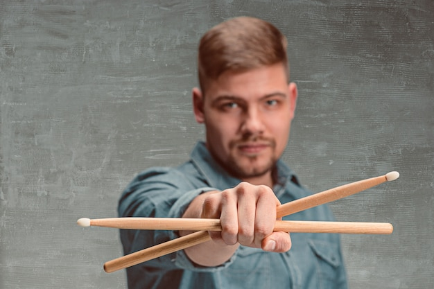 Man holding two drumsticks over gray wall
