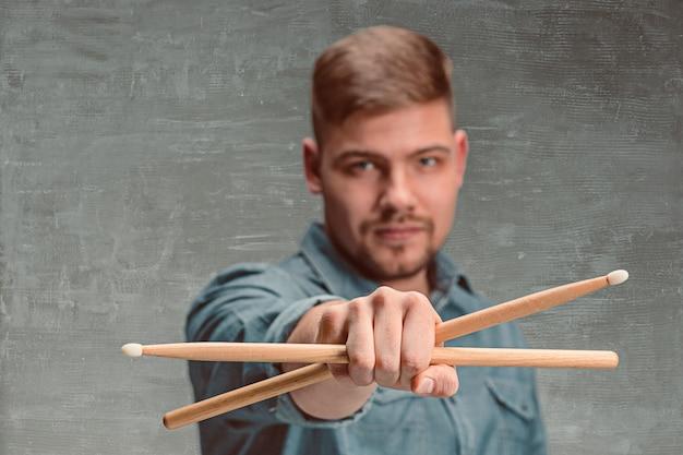Мужчина держит две барабанные палочки над серой стеной
