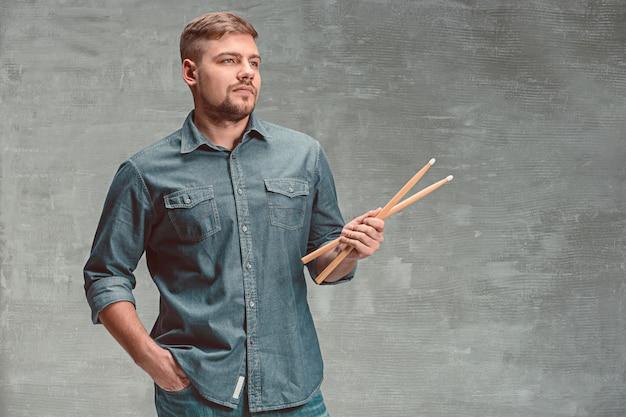 Мужчина держит две барабанные палочки над серым