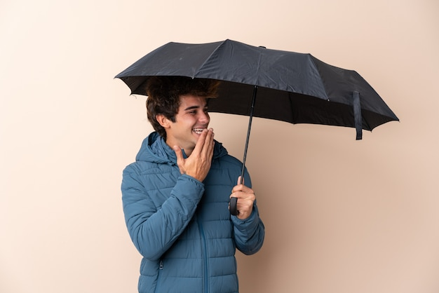 Man holding an umbrella over isolated wall with surprise and shocked facial expression
