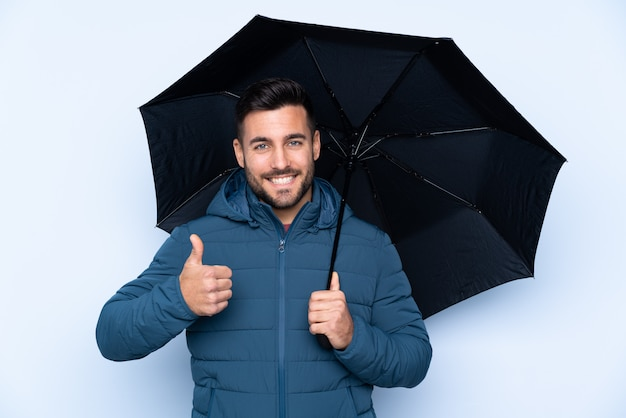Man holding an umbrella over isolated wall with thumbs up because something good has happened