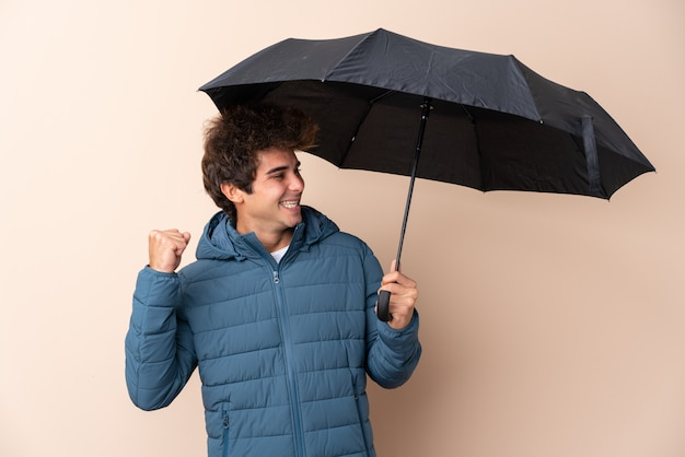 Man holding an umbrella over isolated wall