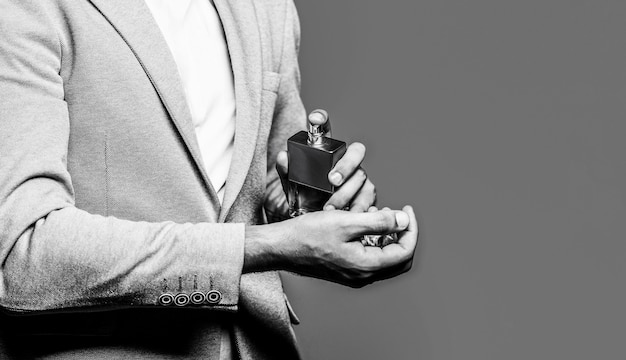 香水のボトルを持っている男。スーツの背景に手に男性の香水。フォーマルなスーツを着た男、香水のボトル、クローズアップ。香りのにおい。ファッションケルンボトル。スペースをコピーします。スペースをコピーします。