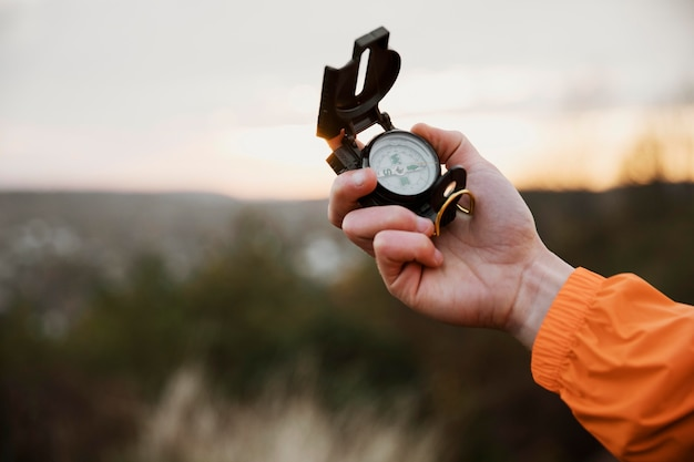 Man holding up compass while on a road trip