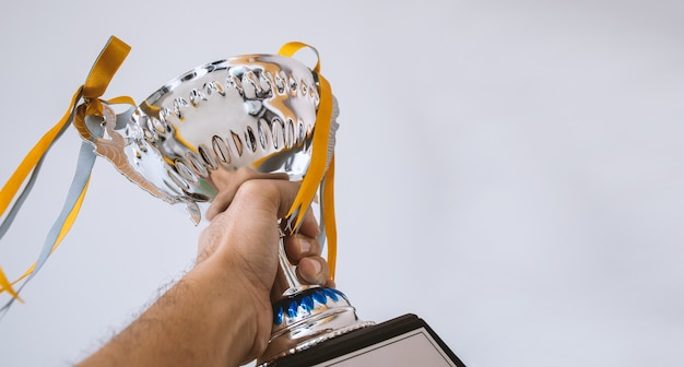 A man holding up a trophy cup