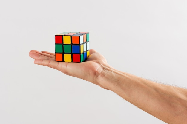 Man holding up an unsolved rubiks cube