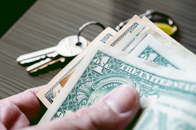 A man holding a us dollar bills in close up photo with keys in composition