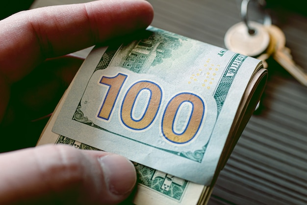 A man holding a us dollar bills in close up photo